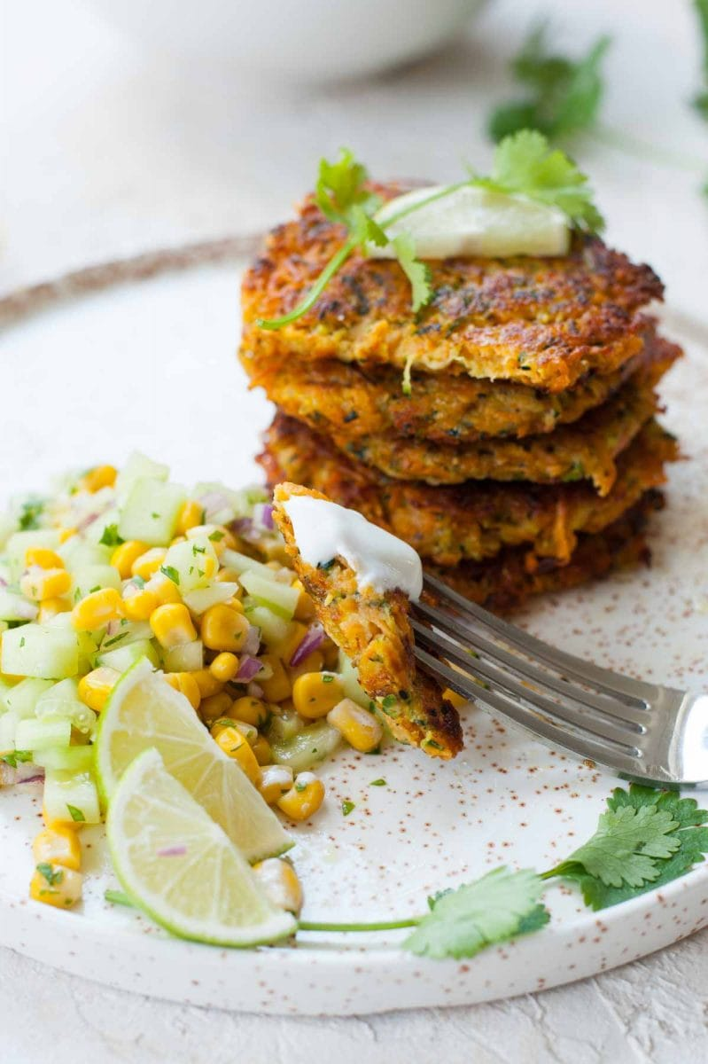 close up shot on sweet potato and zucchini fritters with cucumber corn salsa