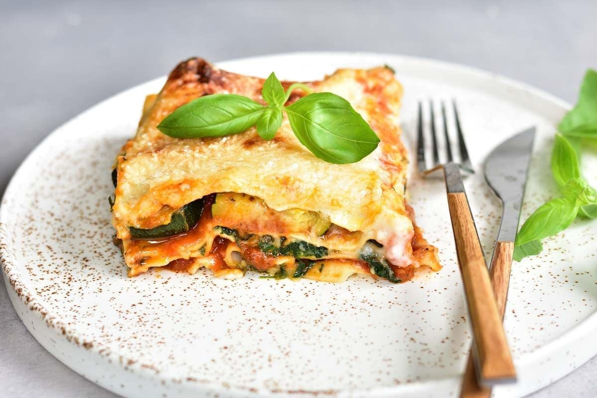 a portion of Vegetarian lasagna with zucchini and spinach on a white plate