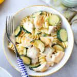 chicken zucchini pasta in a white bowl with a blue fork