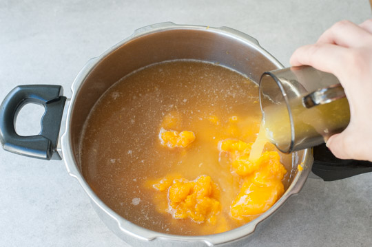 orange juice is being added into a pot