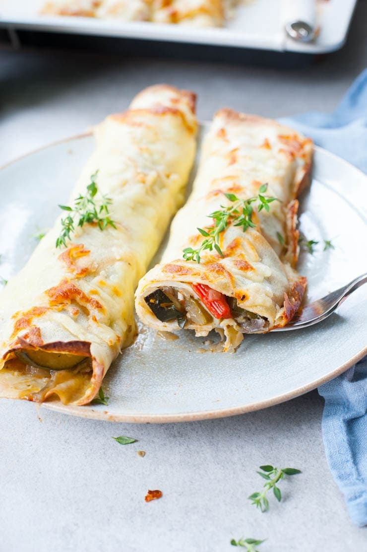 Cheesy vegetable crepes cut in half on a blue plate.