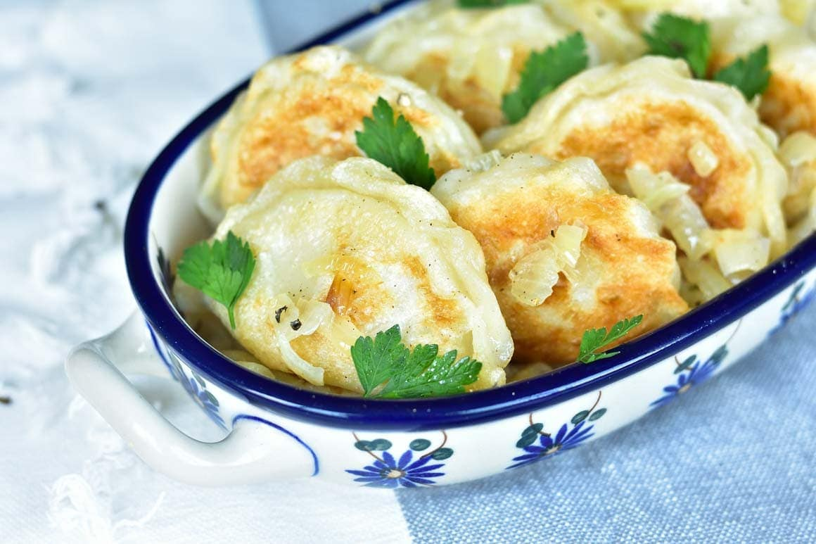 Pierogi ruskie in a blue-white dish, topped with sauteed onion and parsley.