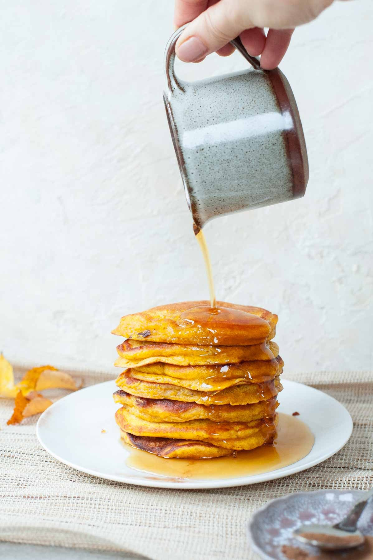 maple syrup is being poured over pumpkin pancakes stack