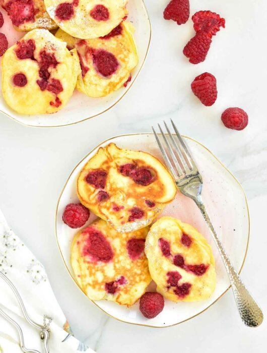 Lemon ricotta pancakes with raspberries on a rose plate.