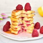 a stack of lemon ricotta pancakes with raspberries