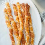 puff pastry cheese straws on a white plate, pumpkin soup in the background