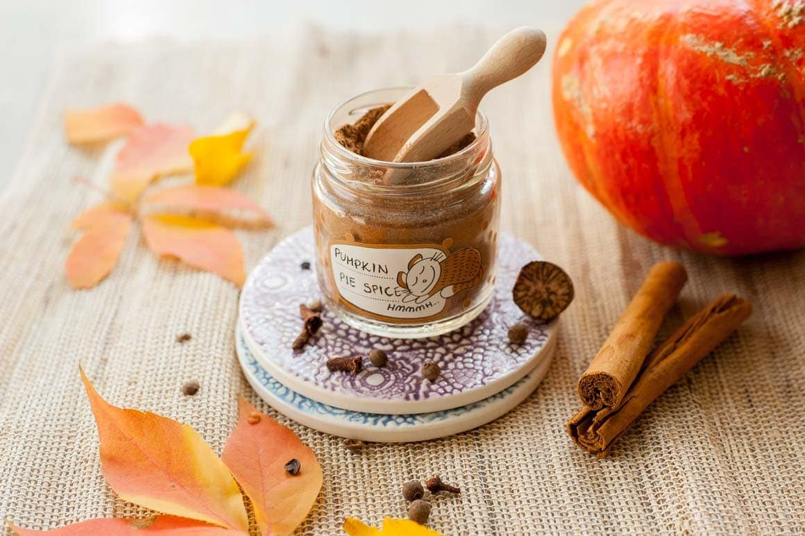 pumpkin pie spice in a small jar, pumpkin, spices and fall leaves in the background