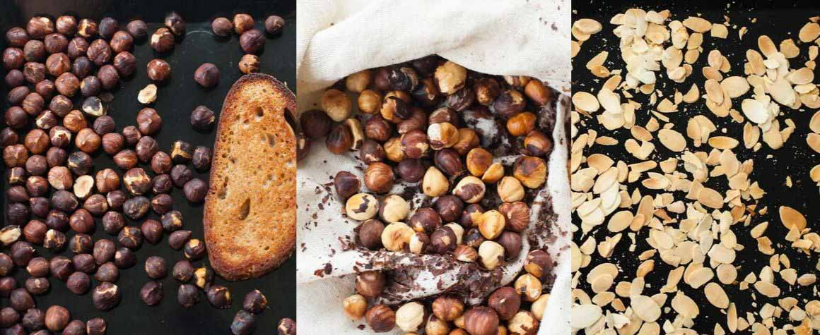 roasted hazelnuts and almonds on a black sheet pan