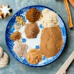 ingredients for gingerbread spice mix on a white-blue plate