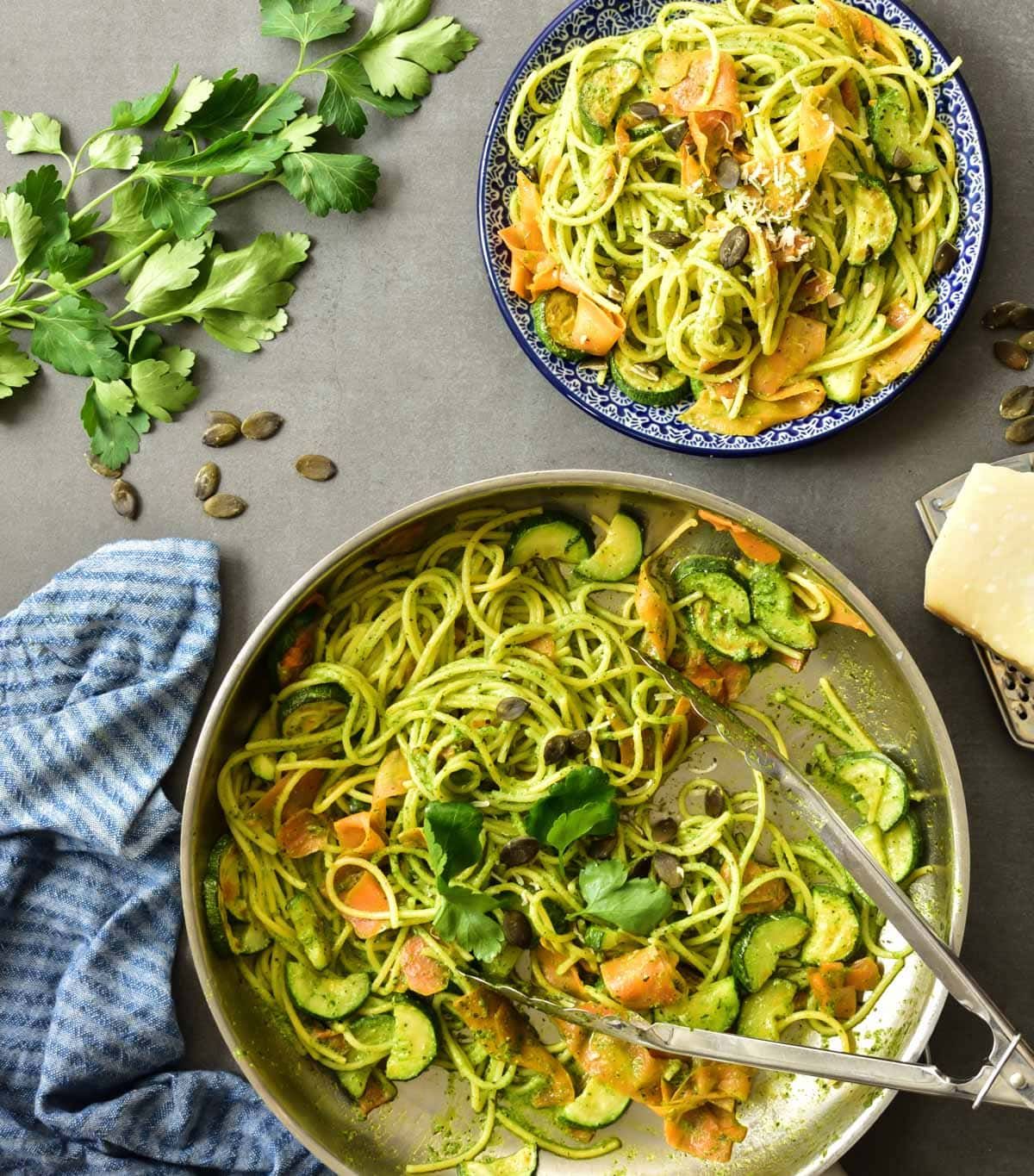 Parsley pesto pasta with zucchini and carrots in a pan and on a plate.