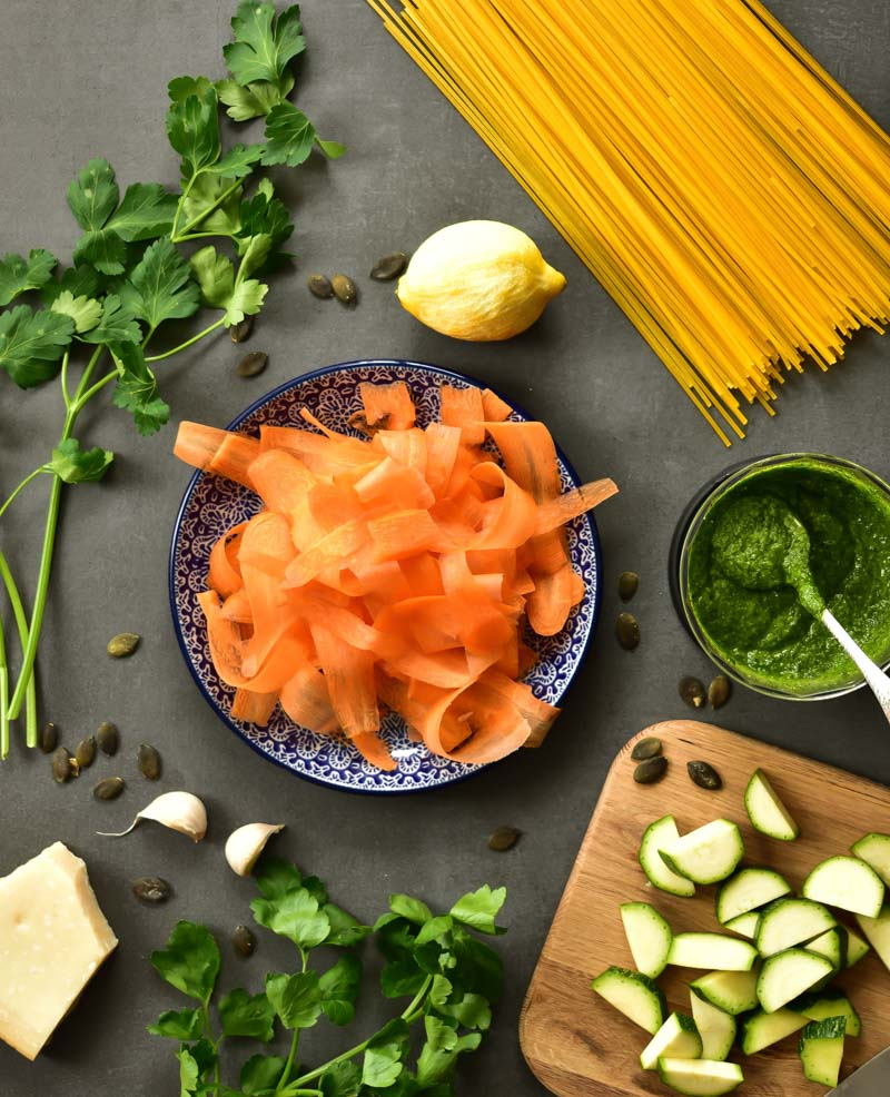 Ingredients needed to prepare parsley pesto pasta with zucchini and carrots.