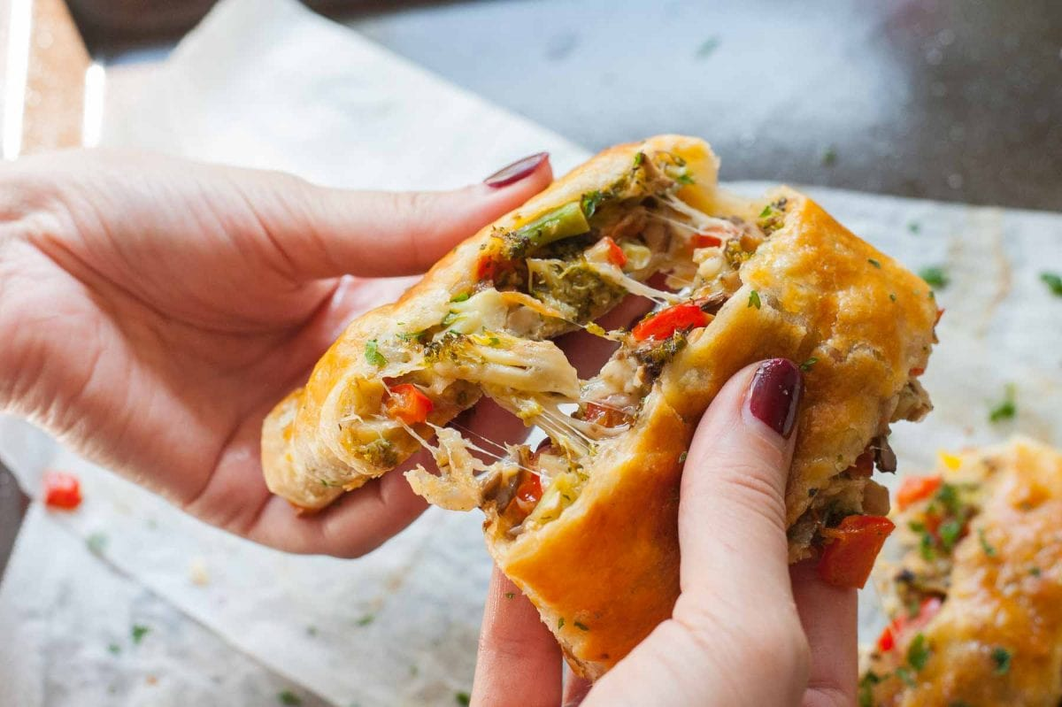 Puff pastry strudel with vegetables and cheese in hands