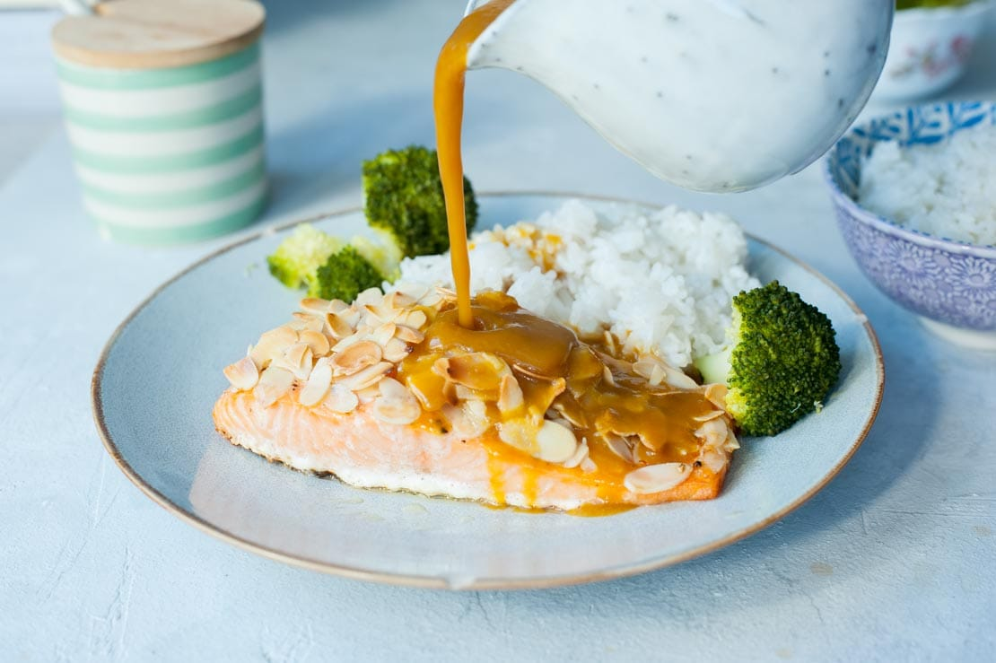 orange ginger sauce is being poured over salmon with almonds