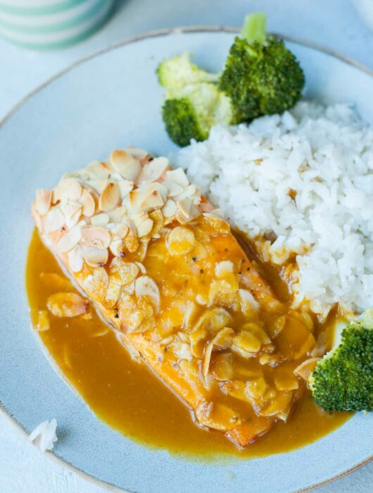 a piece of salmon covered in flaked almonds with orange ginger sauce, coconut rice and broccoli on a blue plate