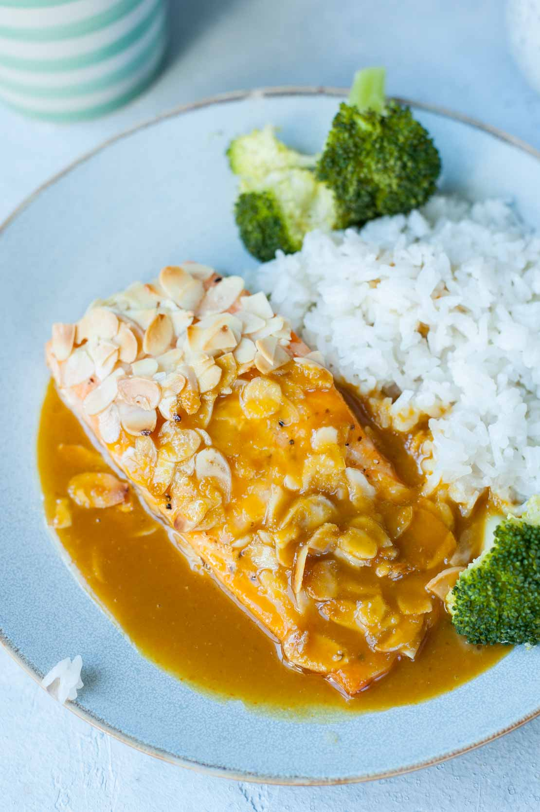 A close up picture of salmon with almonds and orange ginger sauce, served with coconut rice.