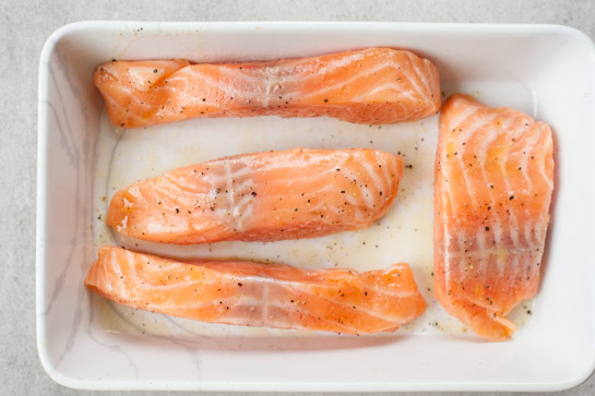 Raw salmon fillets in a baking dish.