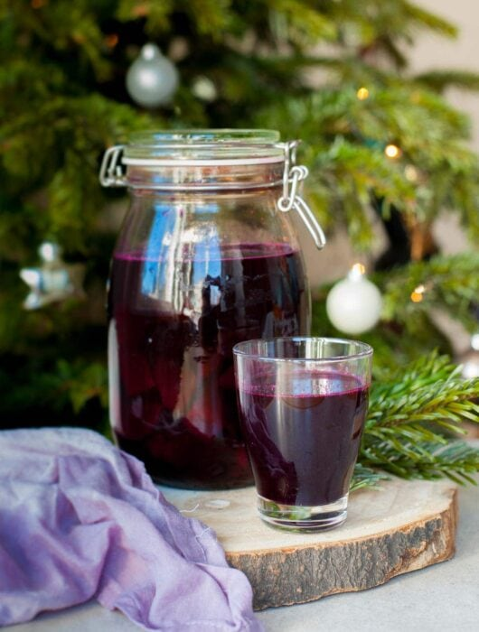 a big jar and a small glass filled with beet kvass, Christmass tree in the background