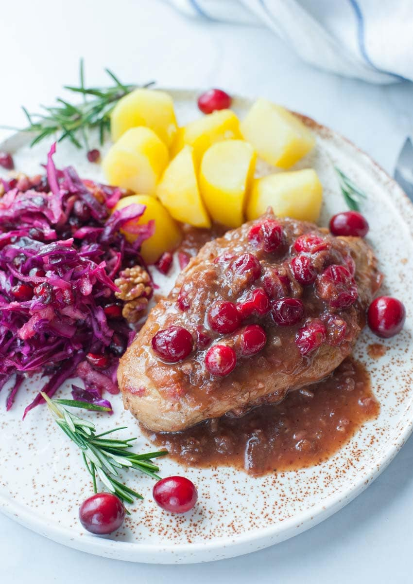Cranberry balsamic chicken on a plate with cooked potatoes and red cabbage slaw