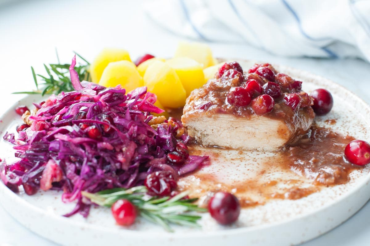 Kurczak w sosie balsamicznym z żurawiną na talerzu z ziemniakami i surówką z czerwonej kapusty