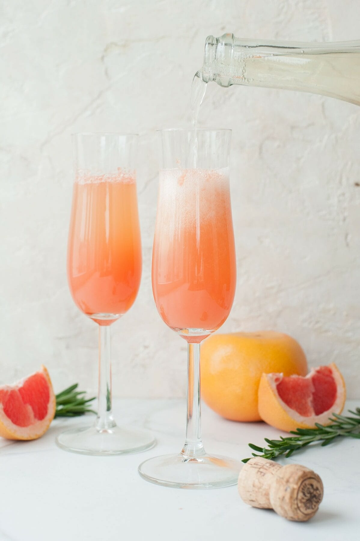 champagne is being poured over grapefruit juice in a champagne glass