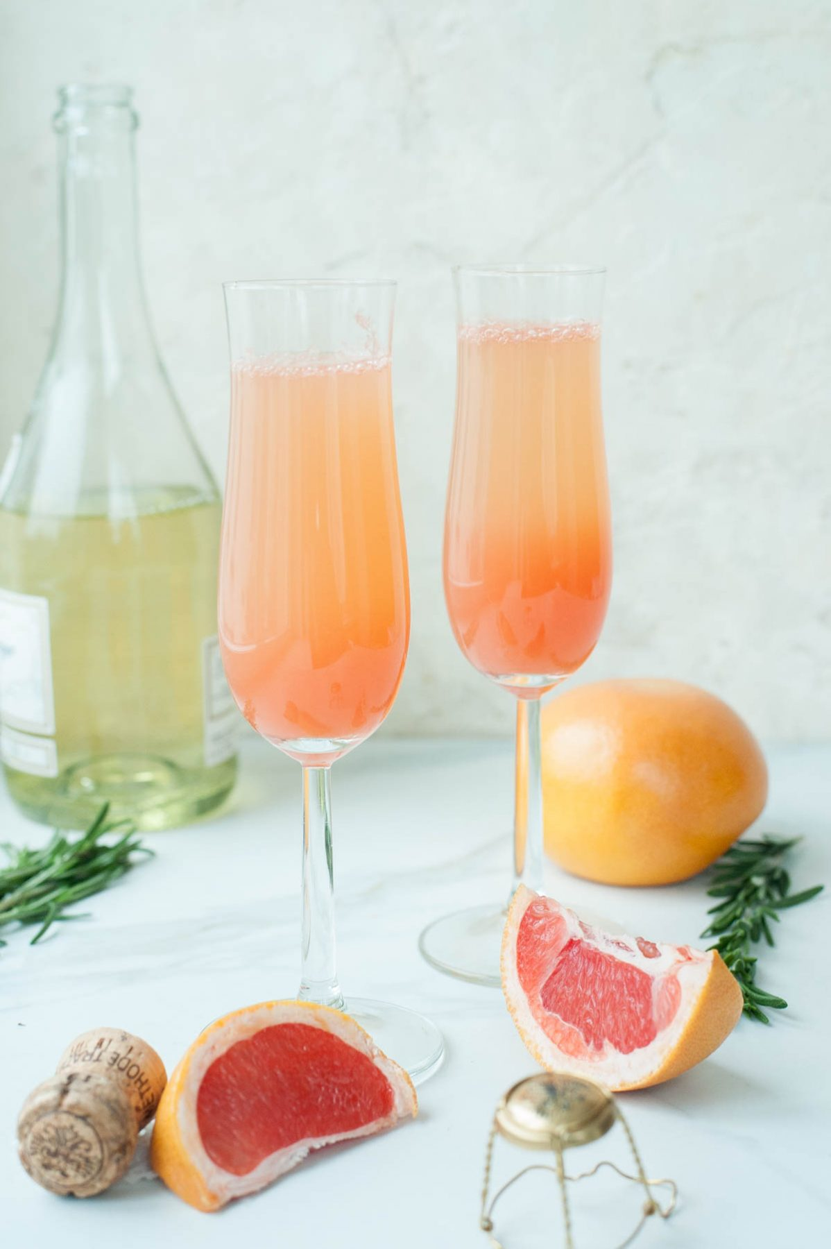 two champagne glasses filled with grapefruit mimosa, grapefruit, rosemary and champagne in the background
