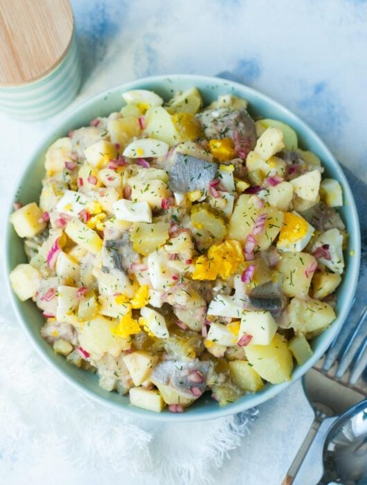 herring salad with potatoes and eggs in a green bowl