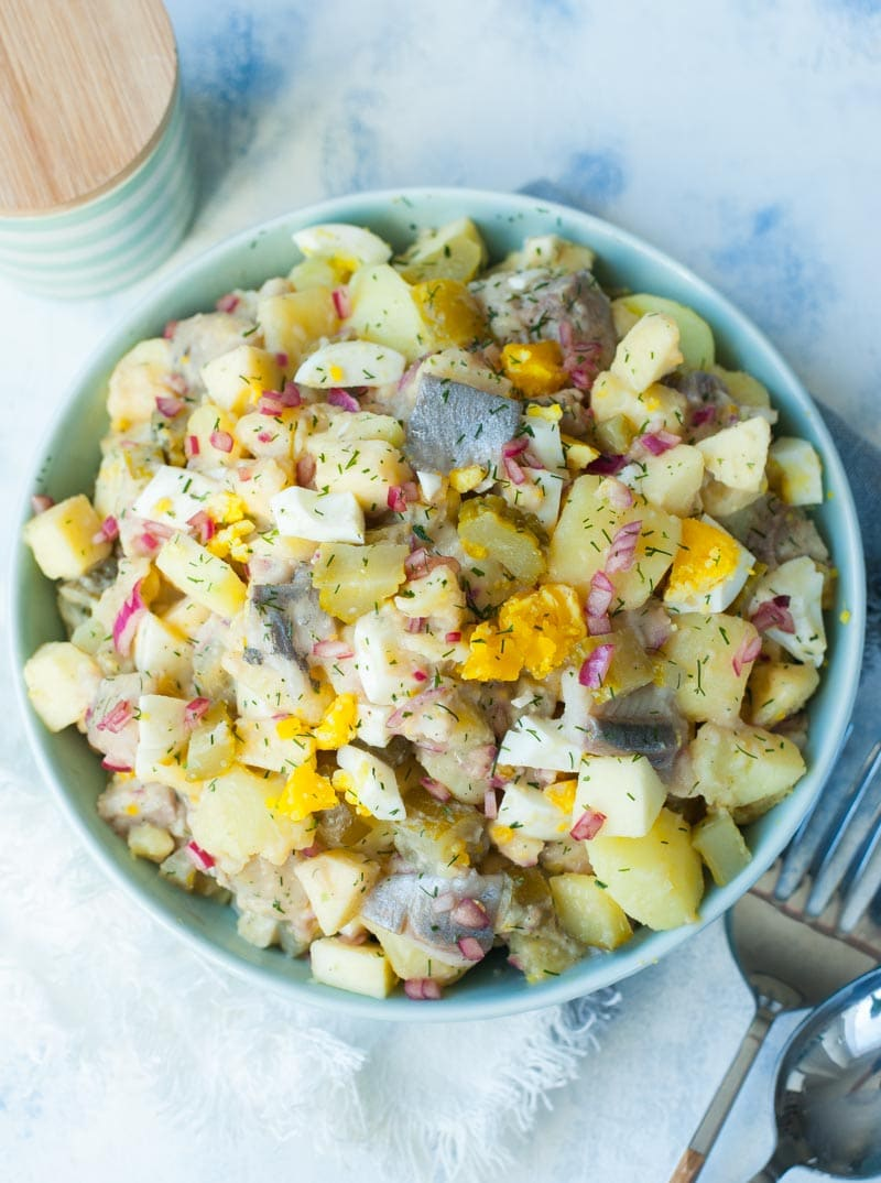 Herring salad with potatoes, eggs, cucumbers in brine and apples