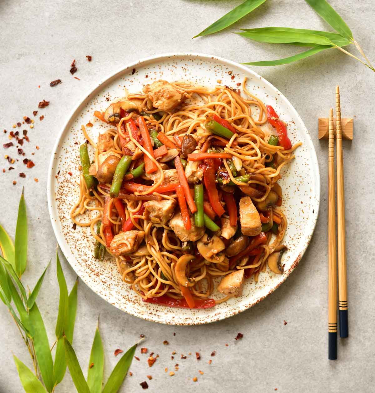 Sweet and sour chicken with noodles and vegetables on a white plate