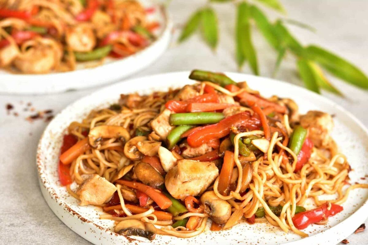 close up shot on sweet and sour chicken with noodles and vegetables on a white plate
