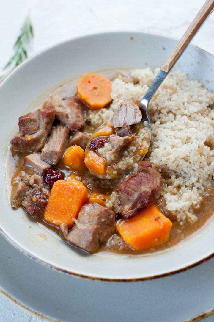 Turkey stew with sweet potatoes and cranberries with pearl barley in a grey plate.