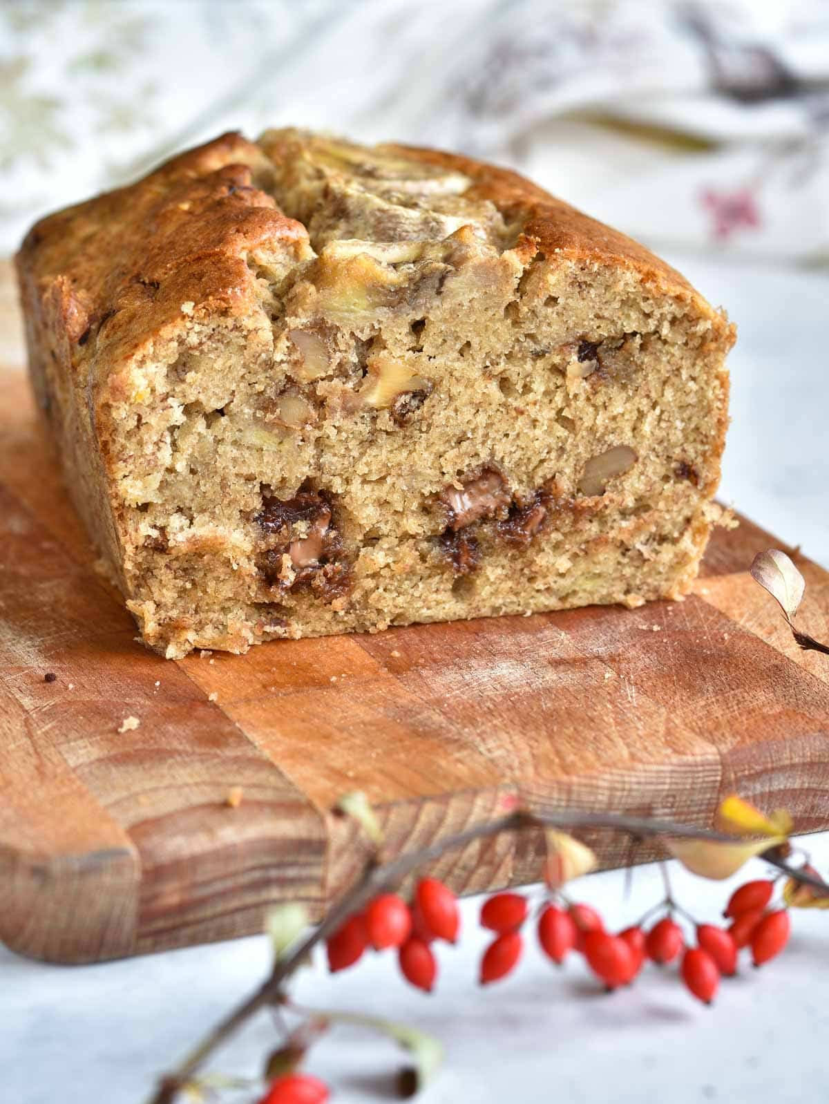 banana bread with chocolate and nuts cut in half on a chopping board