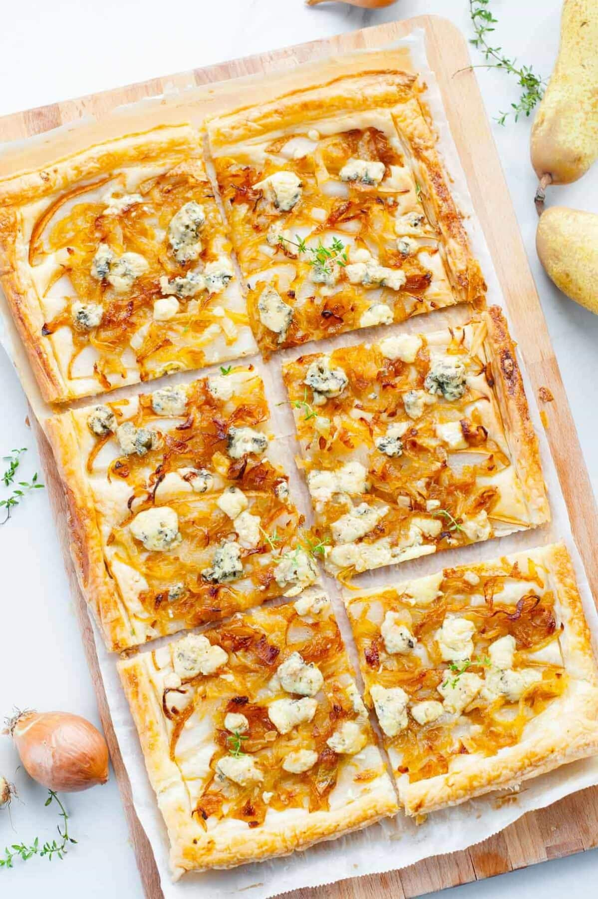 Puff pastry onion tart with pear and blue cheese cut into squares