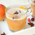 spiced apple cider in a glass, apples and spices in the background