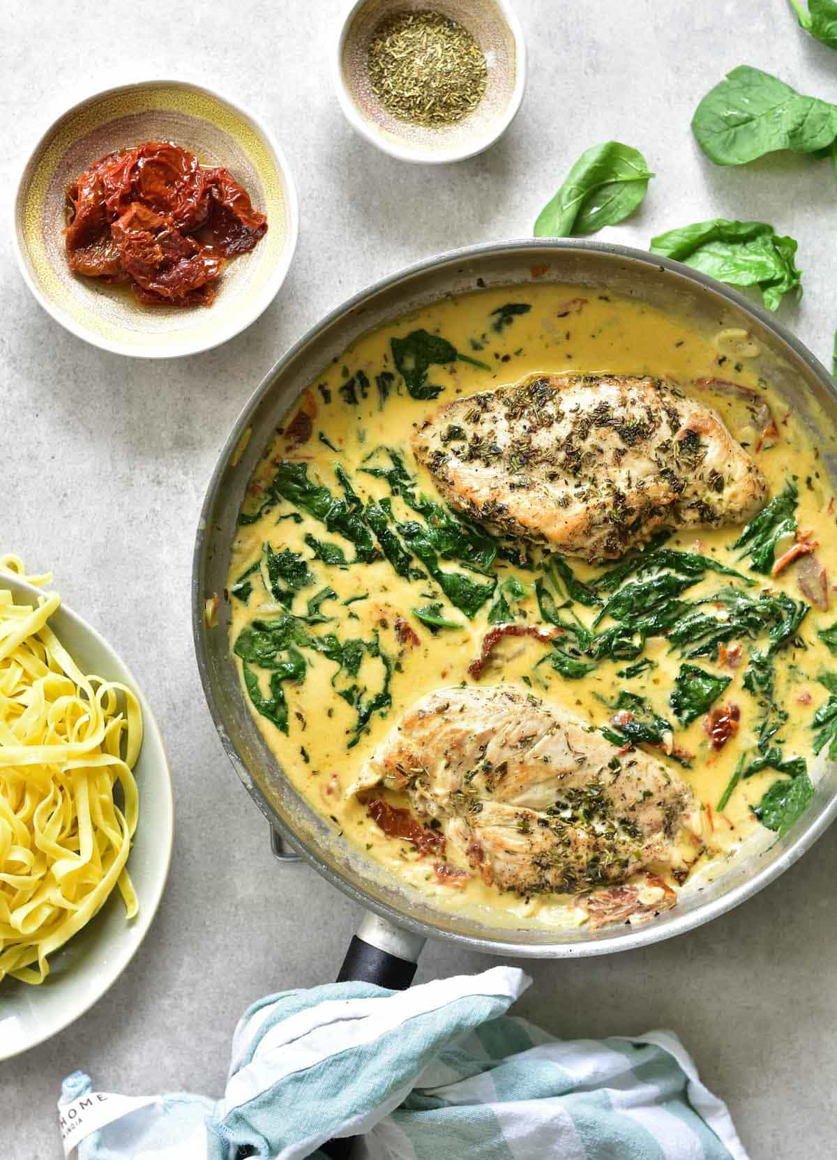chicken breast in creamy sun-dried tomato and spinach sauce on a big pan