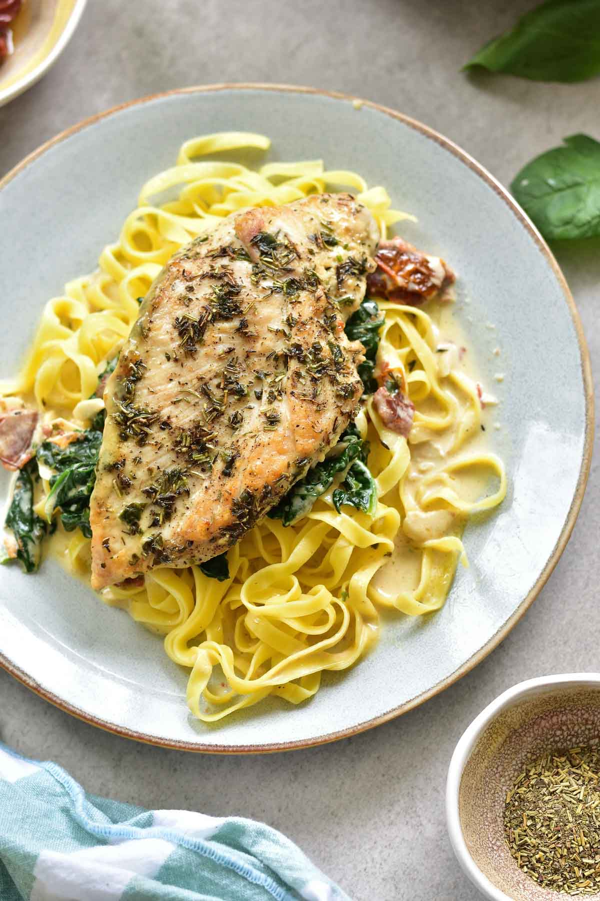 chicken in creamy sun-dried tomato and spinach sauce, served with linguini on a plate