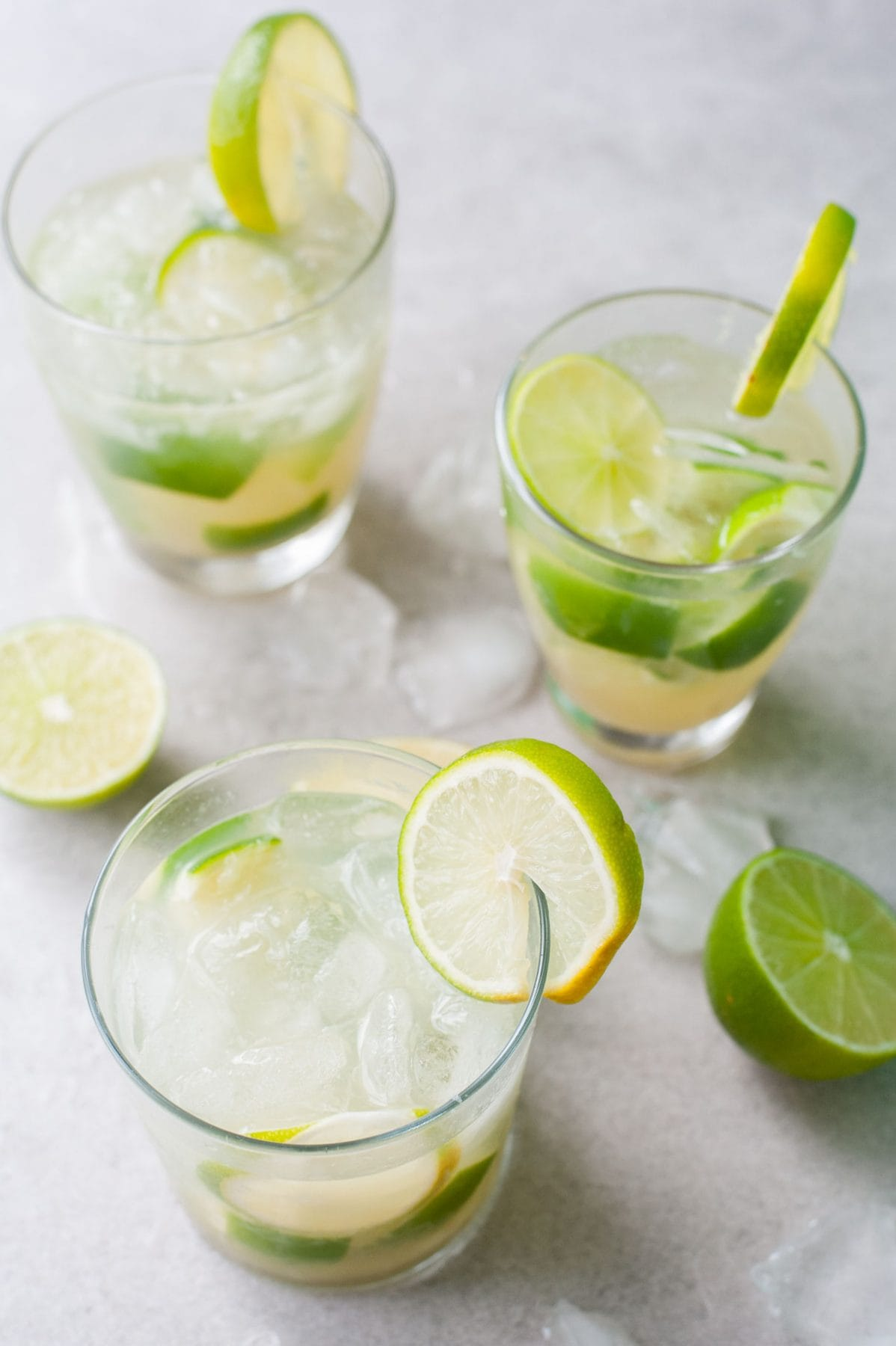 3 glasses with caipirinha, limes and ice around the glasses