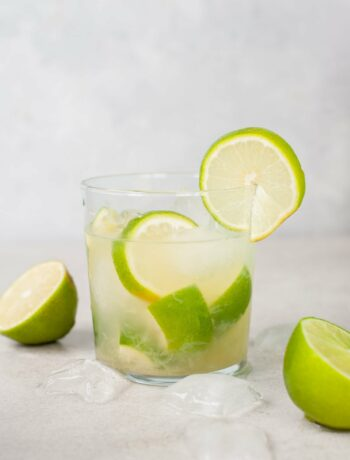 caipirinha in a glass, ice cubes and limes in the background