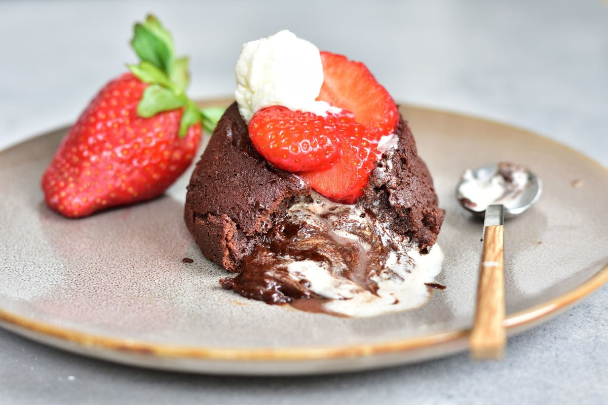Chocolate lava cake on a plate with strawberries and whipped cream