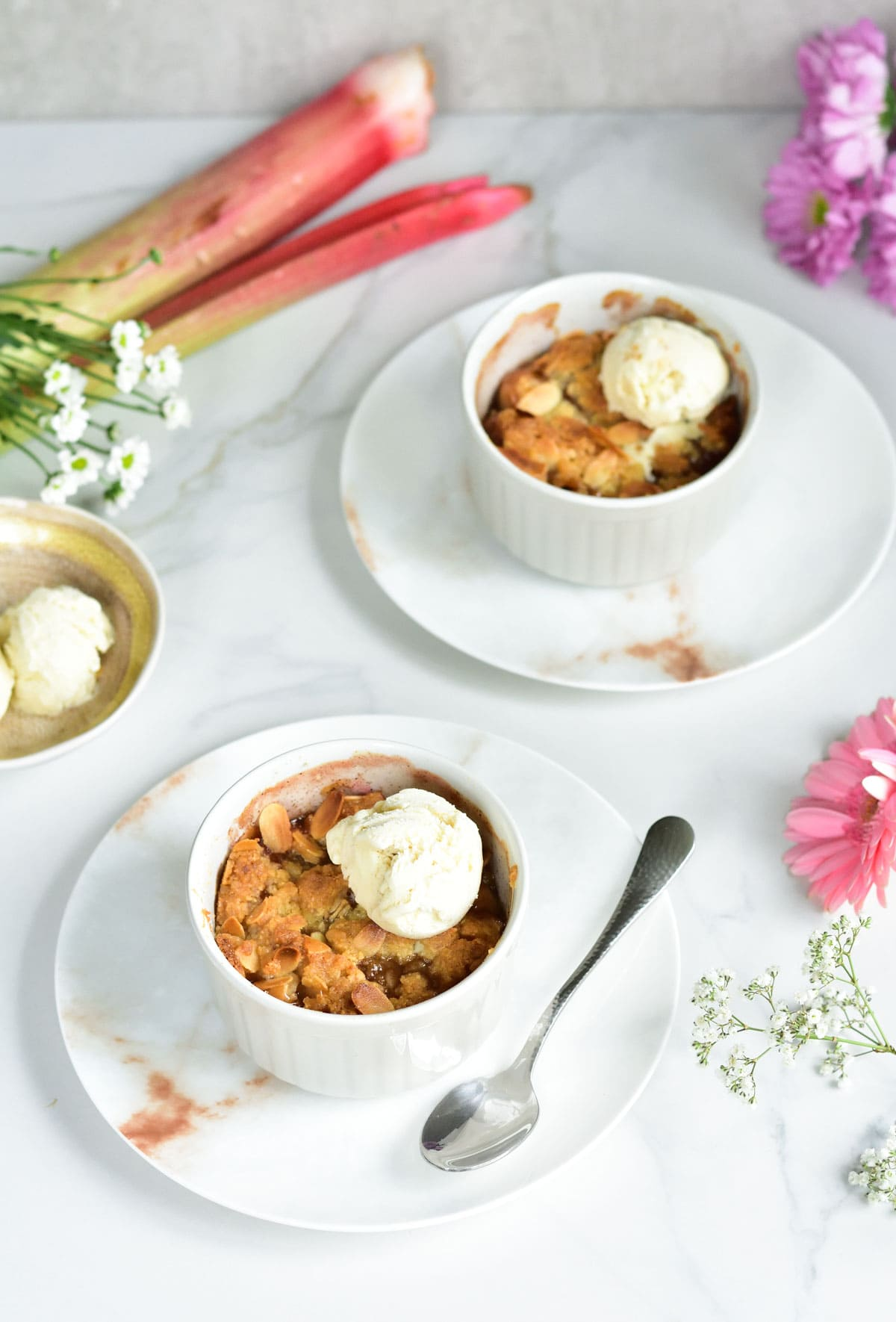 2 ramekins with rhubarb crumble, flowers scattered around