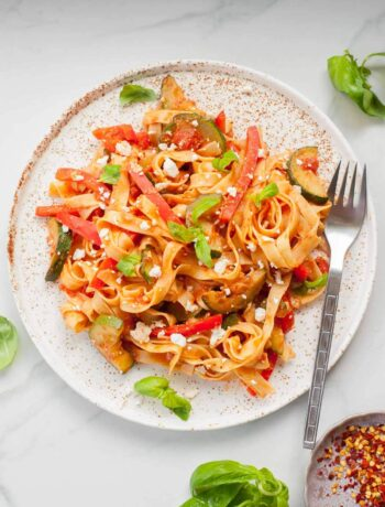 tagliatelle pasta with zucchini, bell pepper and feta on a white plate