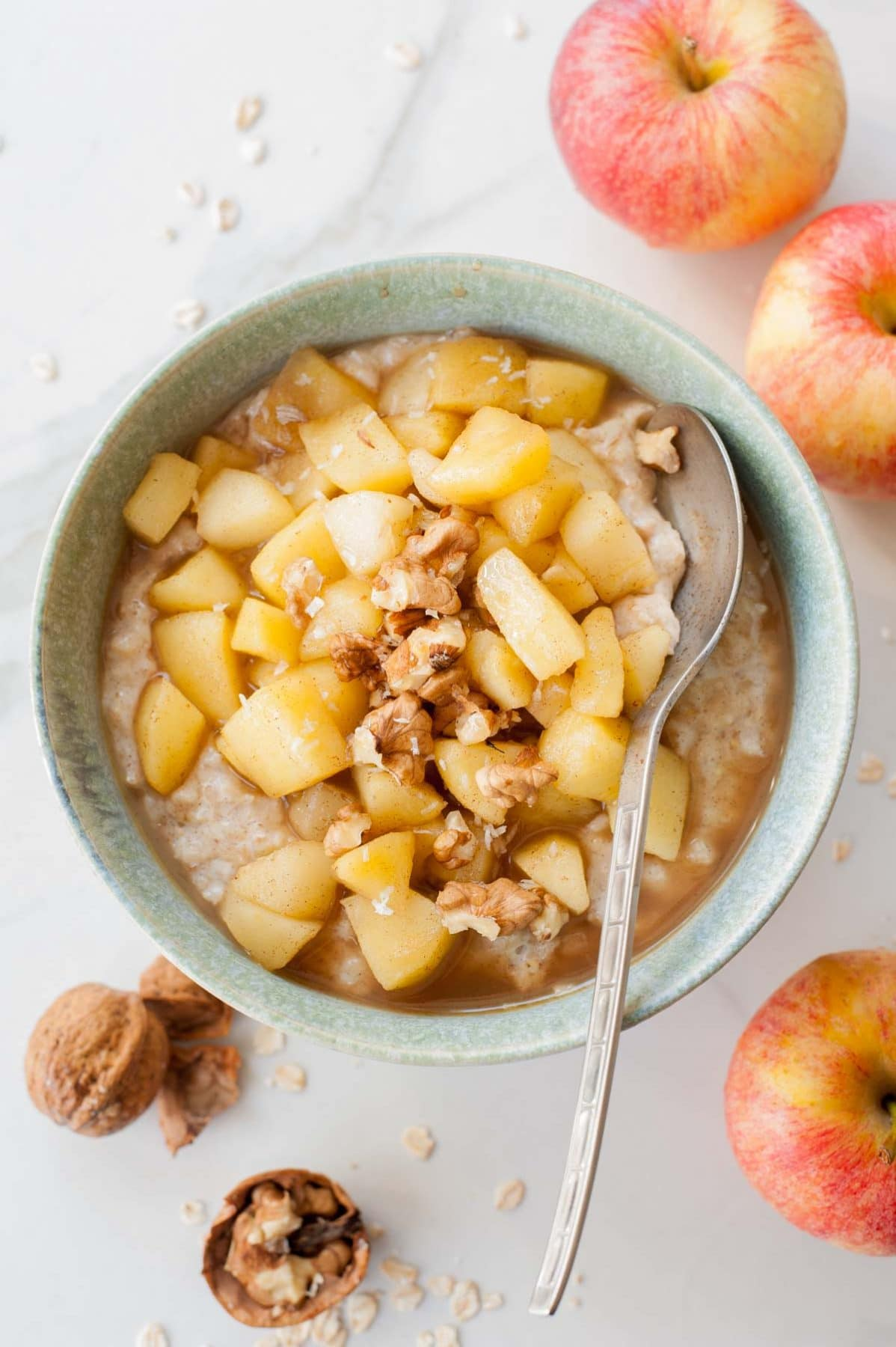 apple cinnamon oatmeal in a green bowl, walnuts and apples scattered around