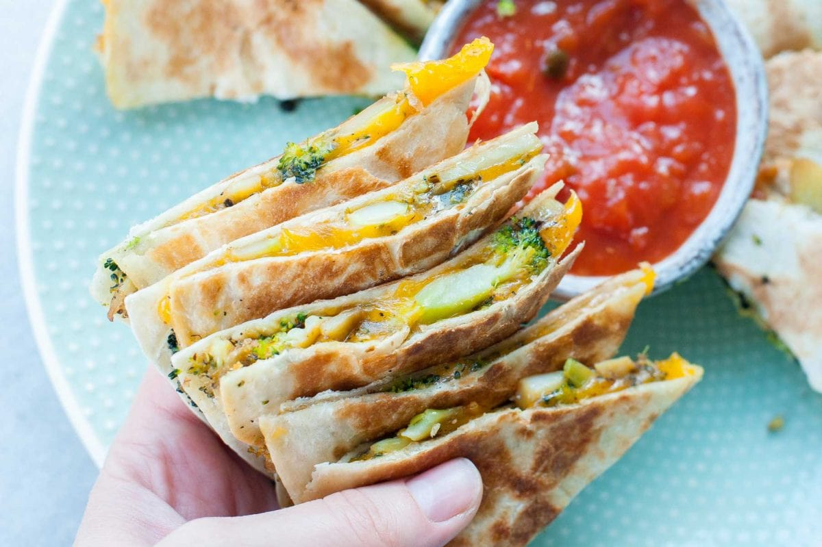 broccoli cheddar quesadillas are being held in a hand, tomato salsa in the background