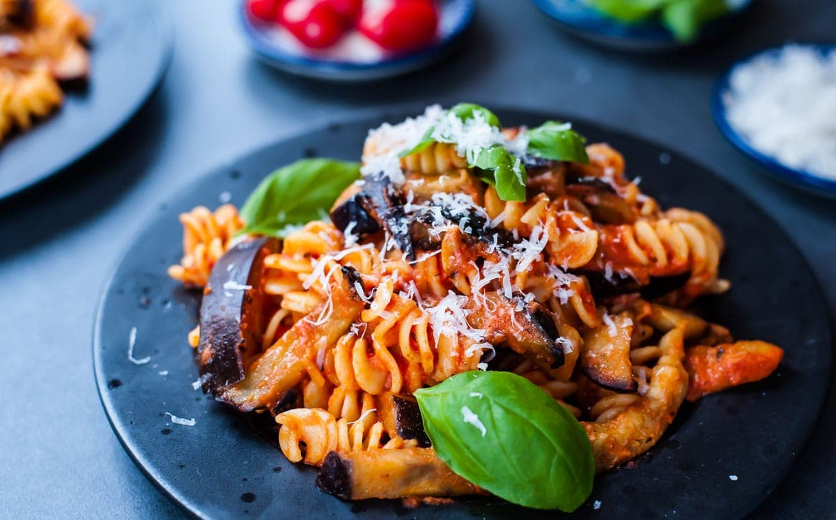 tomato and eggplant pasta on a black plate