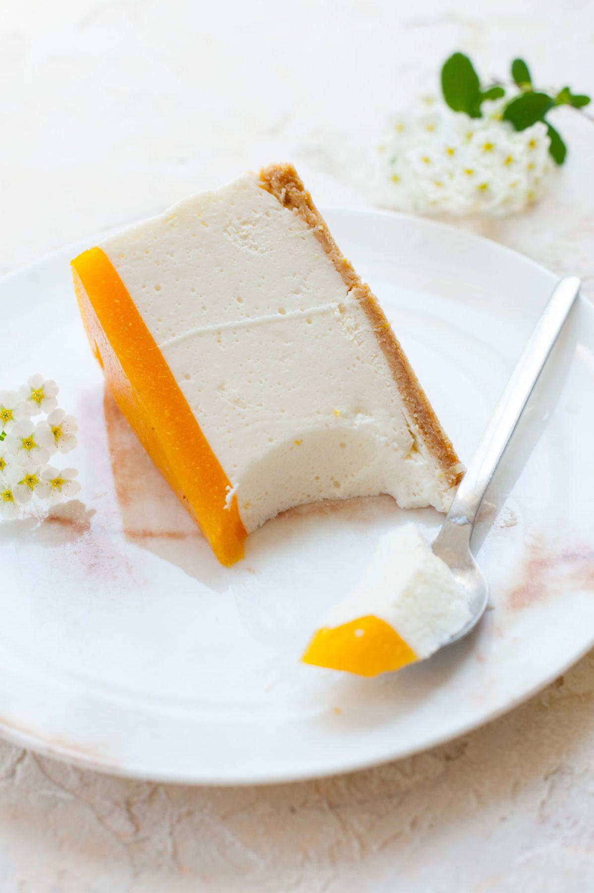 kawałek sernik bez pieczenia z jogurtów greckich z musem morelowym na białym talerzu