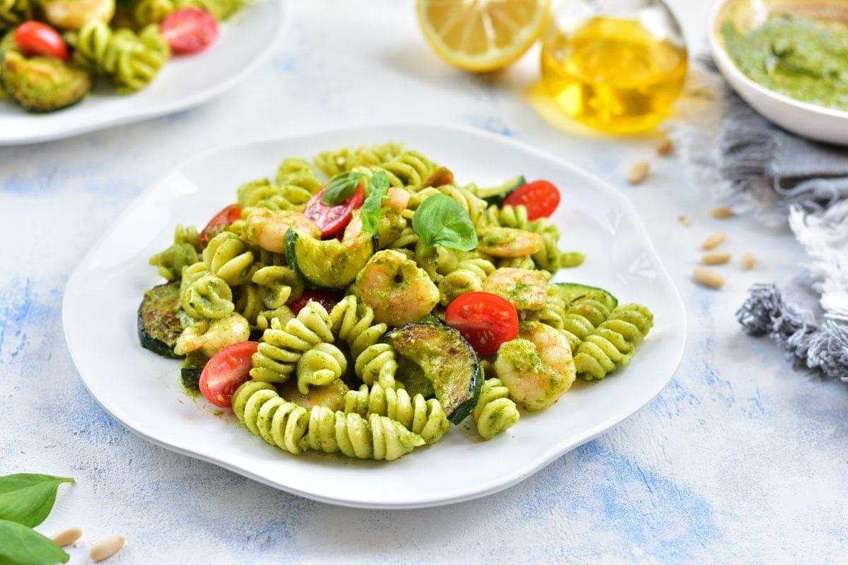 Shrimp pesto pasta with zucchini on a white plate