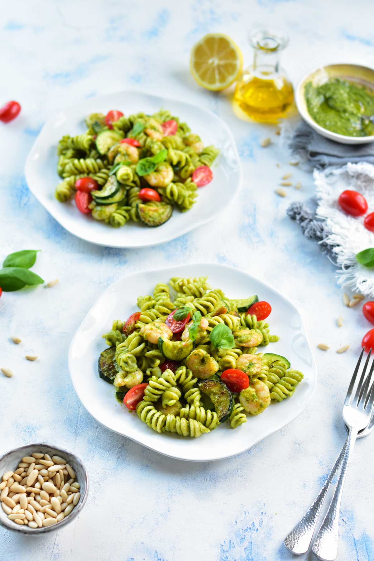 two plates with shrimp pesto pasta on a light blue background