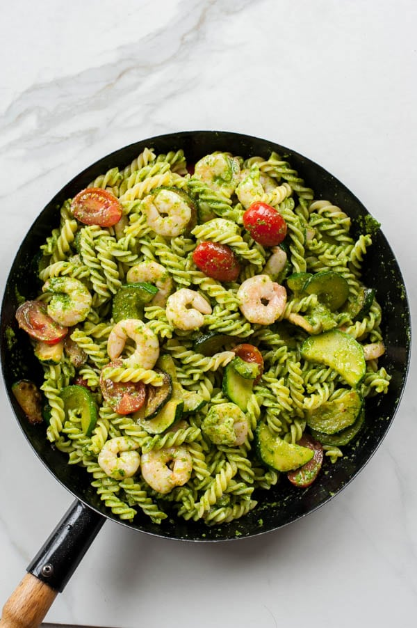 ready shrimp pesto pasta with zucchini in a black frying pan