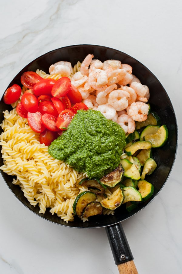all the ingredients for the shrimp pesto pasta in a black frying pan