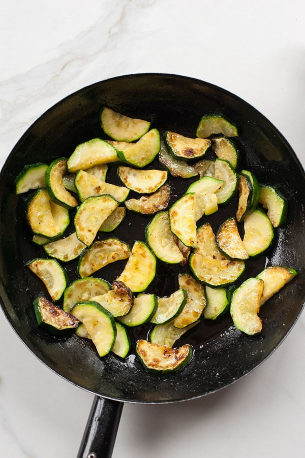 cooked zucchini in a black frying pan