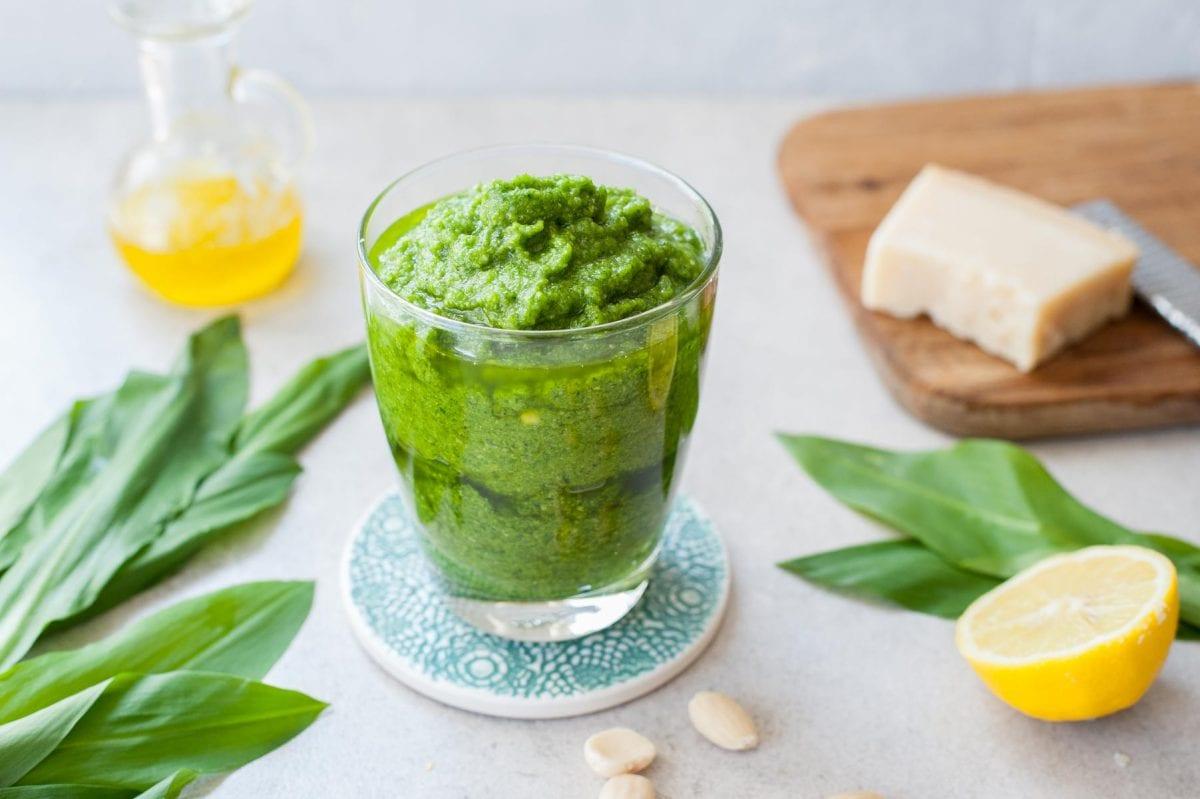 Pesto z czosnku niedźwiedziego w szklance, wokół liście czosnku niedźwiedziego, parmezan i cytryna